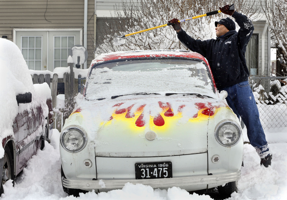 Gary Haley cleans the snow from his vintage 1966 Volkswagen Fastback Monday March 17, 2014 in Berryville, Va. The winter-weary faced another treacherous morning in parts of the Mid-Atlantic as snow and frigid weather blew in just days before the start of spring.