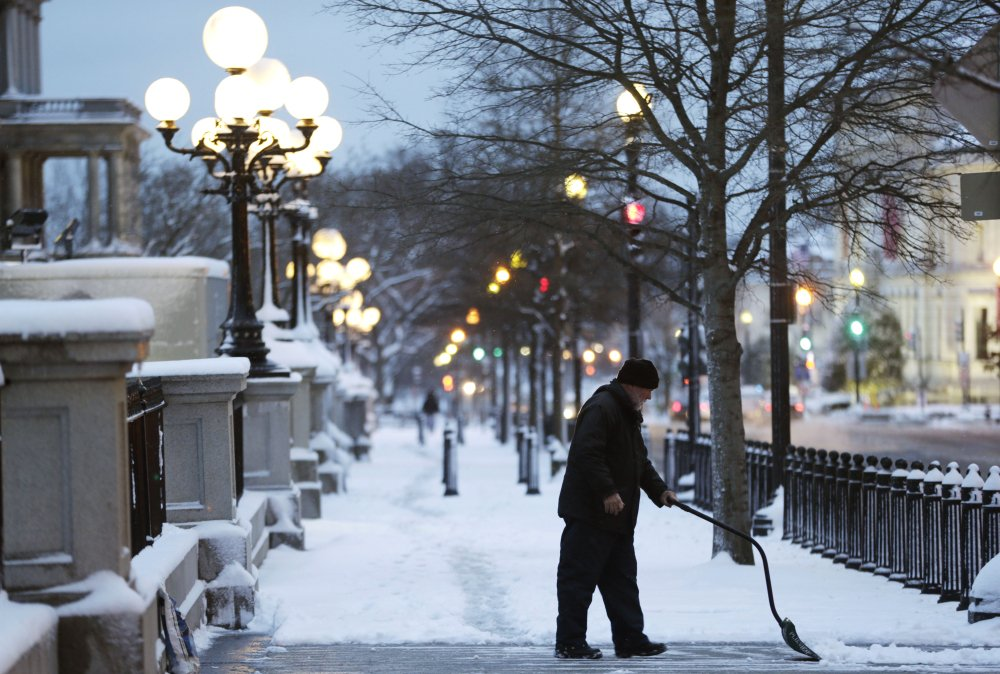 A man clears the sidewalk near the Eisenhower Executive Office Building on the White House complex in Washington, Monday, March 17, 2014, after an overnight snow hit the metro area, prompting area schools the federal and local government to close.