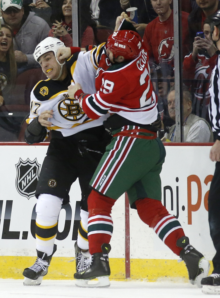 Boston Bruins left wing Milan Lucic, left, and New Jersey Devils left wing Ryane Clowe fight during the first period of an NHL hockey game, Tuesday, March 18, 2014, in Newark, N.J.