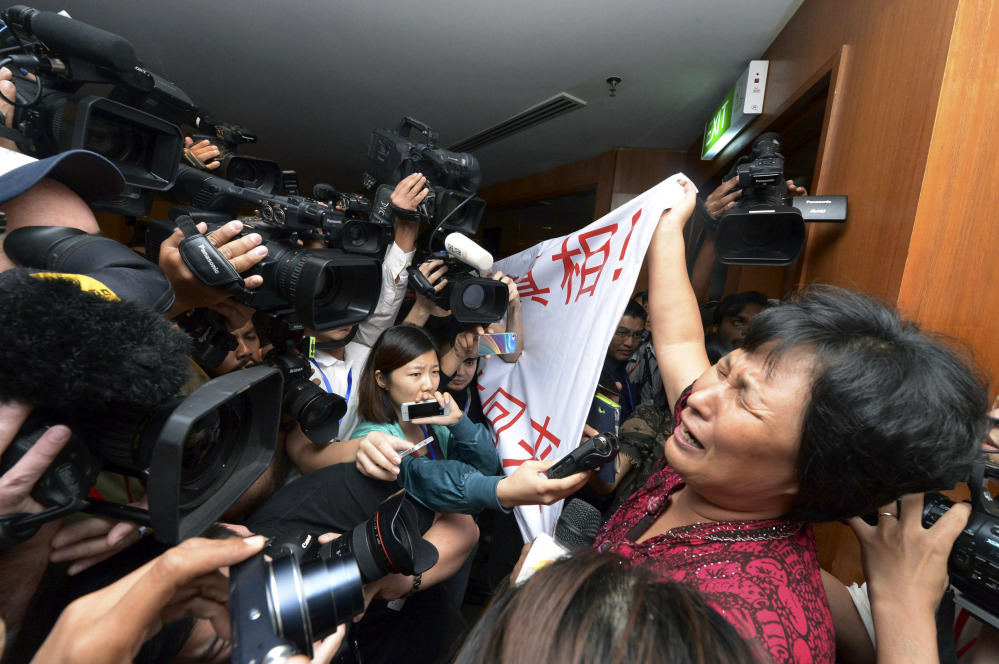 """A Chinese relative of passengers aboard a missing Malaysia Airlines plane cries as she holds a banner in front of journalists reading 'We are against the Malaysian government for hiding the truth and delaying the rescue. Release our families unconditionally!"""" at a hotel in Sepang, Malaysia, Wednesday, March 19, 2014. Malaysian authorities examined new radar data from Thailand that could potentially give clues on how to retrace the course of the Malaysia Airlines plane that vanished early March 8 with 239 people aboard en route from Kuala Lumpur to Beijing. Twenty-six countries are looking for the aircraft as relatives anxiously await news."""