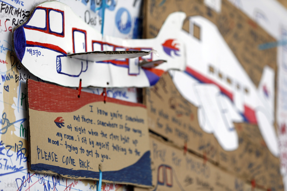 A message card is seen below a paper plane of a Malaysian airliner, on the message board for passengers aboard a missing Malaysia Airlines plane at Kuala Lumpur International Airport in Sepang, Malaysia, Wednesday, March 19, 2014. New radar data from Thailand gave Malaysian investigators more potential clues Wednesday for how to retrace the course of the missing Malaysian airliner, while a massive multinational search unfolded in an area the size of Australia.