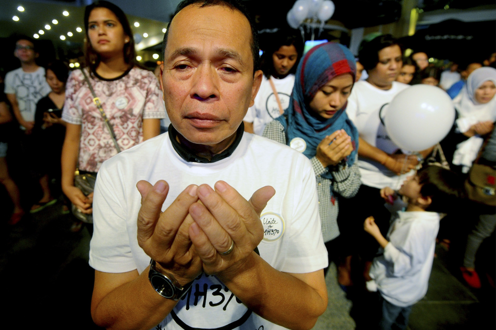 A Malaysian Muslim man prays during an interfaith event for the missing Malaysia Airlines flight MH370 at a shopping mall in Petaling Jaya outside Kuala Lumpur, Malaysia, on Tuesday.