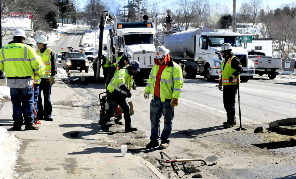 Staff photo by David Leaming GAS WANTED: Employees of Summit Natural Gas of Maine and sub-contractors work on the gas pipeline in the center of Norridgewock on Monday, March 17, 2014. The company has announced another delay in connecting with UPM Madison.