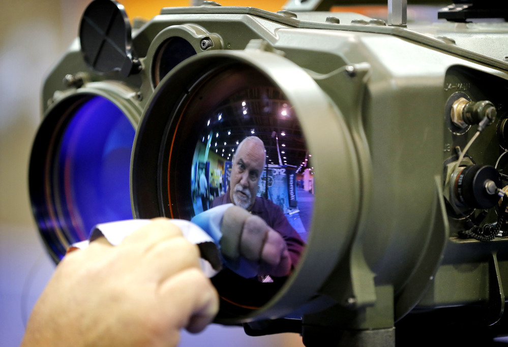 Gary Wagner, of Elbit Systems of America, cleans the lens of a long-range thermal imaging targeting system at the Border Security Expo.