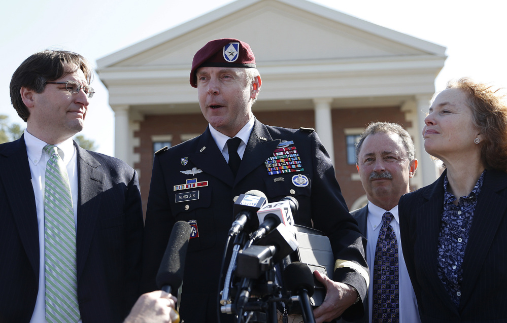 Brig. Gen. Jeffrey Sinclair, who admitted to inappropriate relationships with three subordinates, makes a statement after leaving the courthouse following sentencing at Fort Bragg, N.C., Thursday. Attorneys Lathrop Nelson III, left, Richard Scheff and Ellen Brotman accompany him.