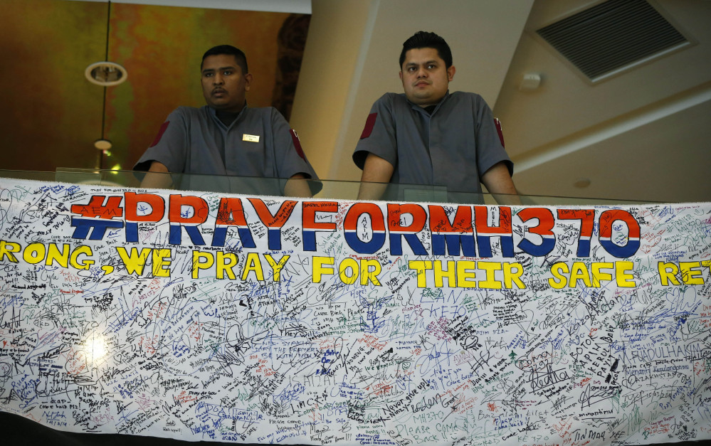 Hotel staff stand next to messages written to people involved with the missing Malaysia Airlines jetliner MH370 at a hotel in Putrajaya, Malaysia, on Thursday.
