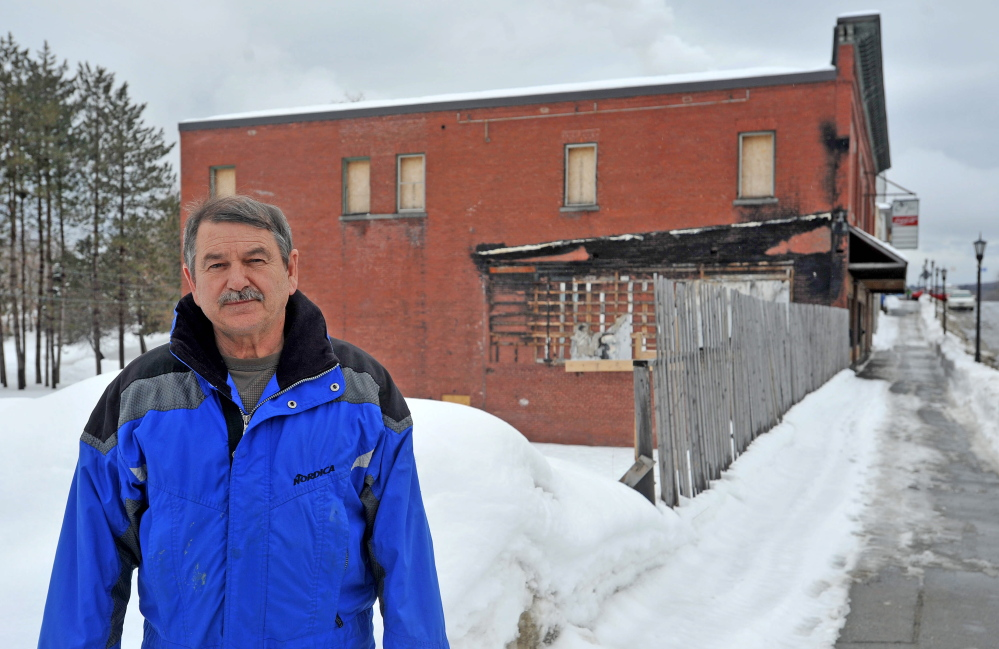FILLING A HOLE: Bob Hagopian, owner of Economy Trophy, stands near the open space left behind from fire two years ago on Main Street in Madison on Thursday.