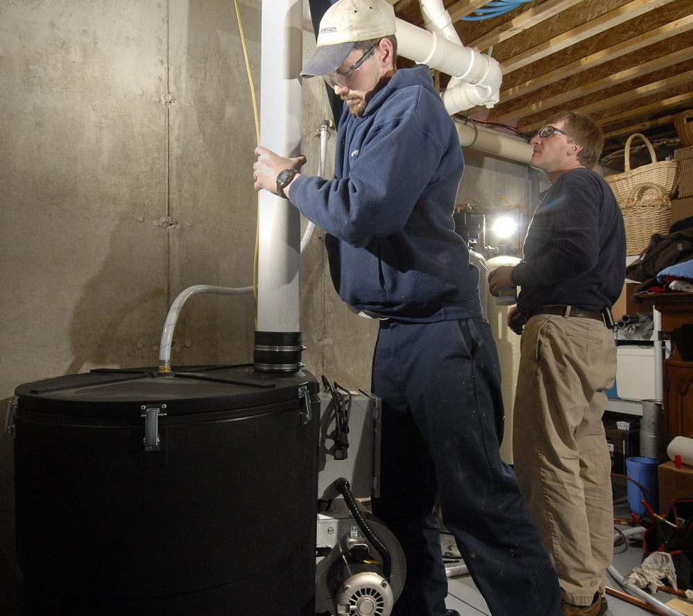 RADON TEST: Shawn Garrity, left, and Scott King of Air & Water Quality Inc., of Freeport, install a radon gas treatment unit in a Maine home in a 2007 file photo. Maine law requires landlords to test for radon in all buildings with rental units, but it's still unclear what agencies will enforce the penalties if they don't.