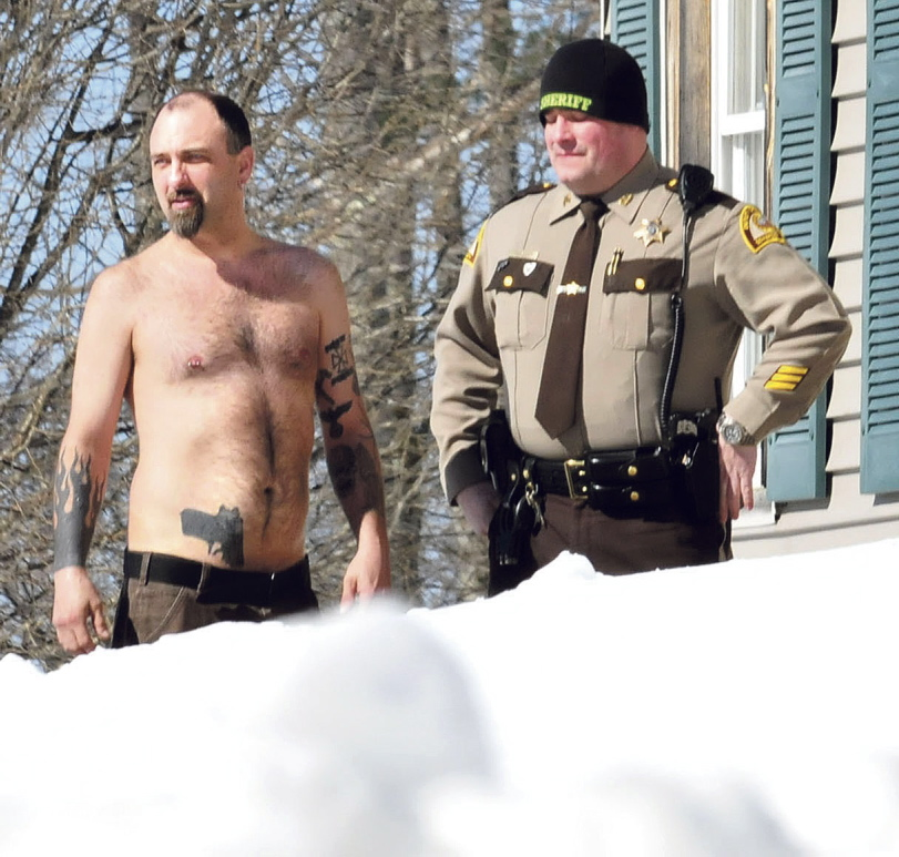 CLOSE CALL: Norridgewock resident Michael Smith stands beside a Somerset County Sheriff deputy after he was coaxed out of his home by police on Tuesday. The tattoo of a pistol on his stomach was mistaken for a real firearm by employees of Lucas Tree Experts, who called police.