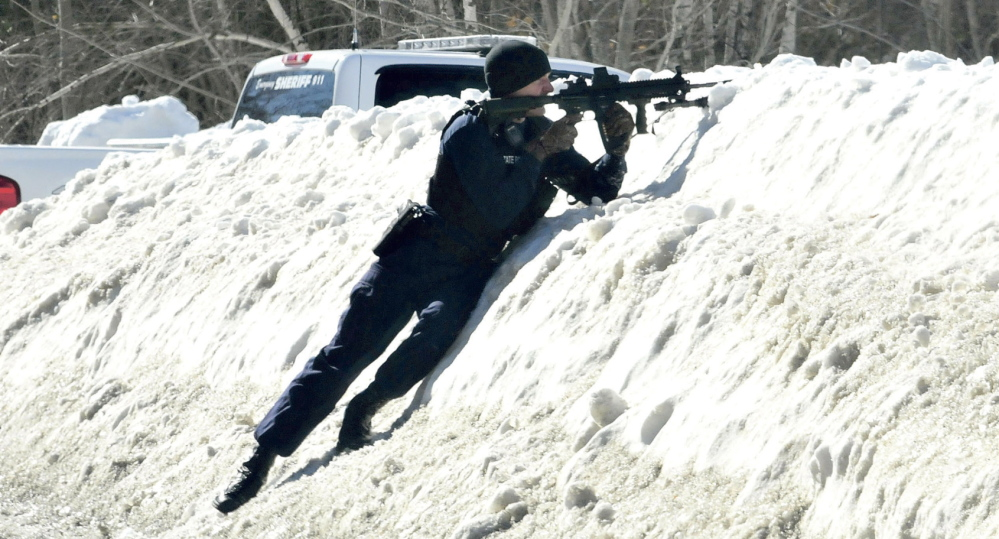 ARMED: Trooper Scott Duff trains his rifle toward the home of Michael Smith as other police called for him to come out of the home in Norridgewock on Tuesday. Tree workers called police earlier after they encountered Smith regarding cutting wood under power lines and mistook a pistol tattoo as a real firearm.
