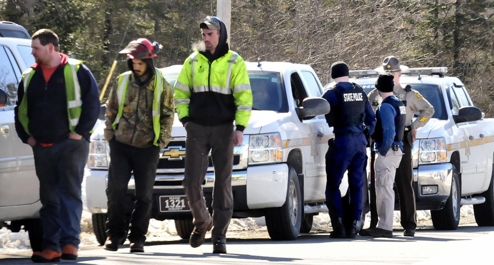 POLICE SUMMONED: Three employees of Lucas Tree Experts walk away after talking to state troopers and Somerset County sheriff deputies who were discussing how to approach nearby resident Michael Smith on Tuesday. Smith had told the workers to leave his property and not cut wood under power lines and the workers mistook a tattoo of a gun on Smith's stomach for a real one and called