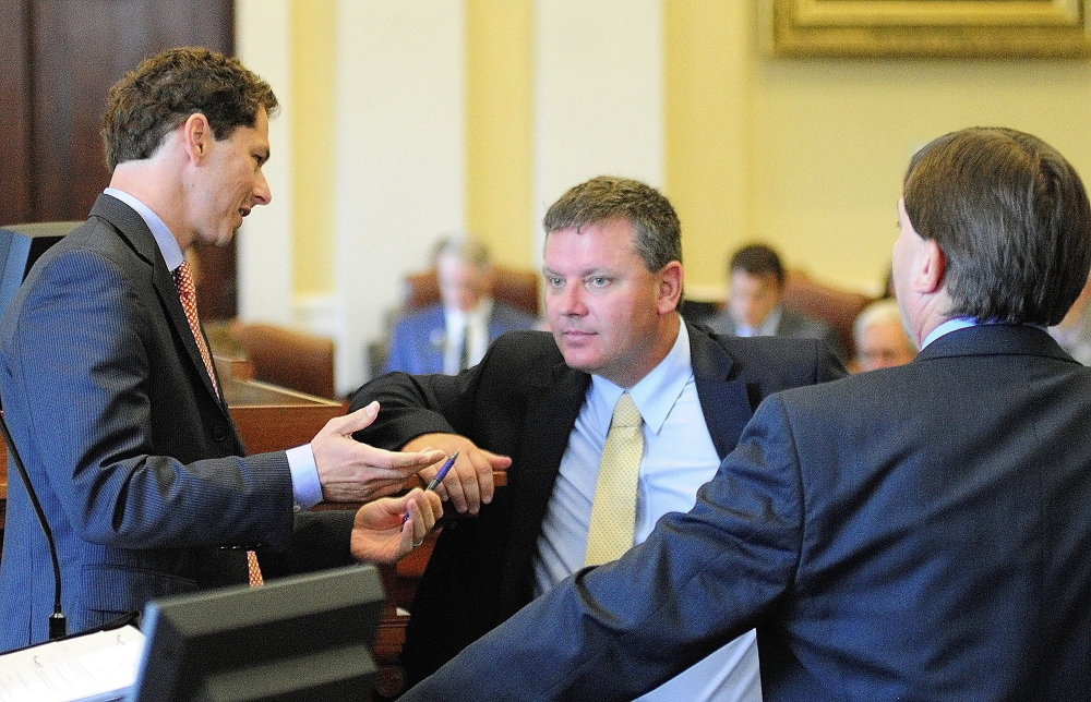 At the races: Senate President Justin Alfond, D-Portland, left, confers with Senate leaders Sen. Michael Thibodeau, R-Winterport, and Sen. Troy Jackson, D- Allagash, during an August special session in the State House in Augusta. Thibodeau is leading Republican efforts to take back the majority from the Democrats this election season.