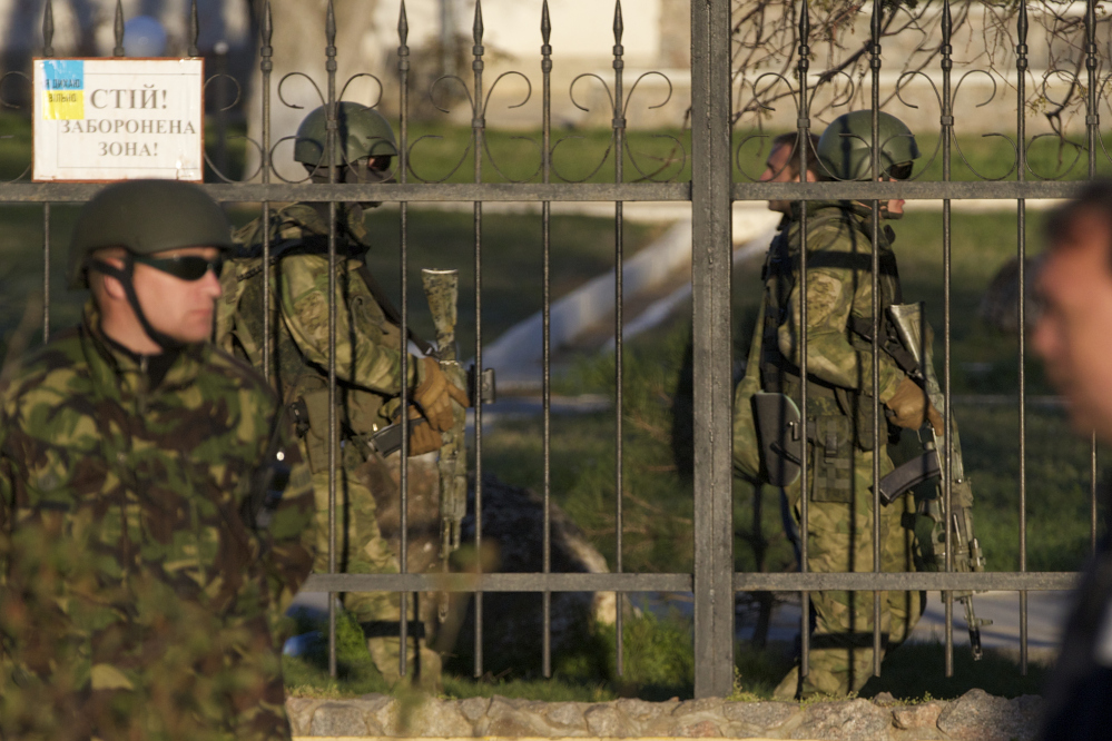 Russian soldiers walk inside the Belbek airbase, outside Sevastopol, Crimea, on Saturday. Russian forces used at least four armored vehicles to break into an air base here, seizing control of one of the last Ukrainian military outposts in Crimea. After an hours-long tense standoff between Russian and Ukrainian forces, gunfire and explosions could be heard as the vehicles broke down the gate at the air base located just outside Sevastopol.