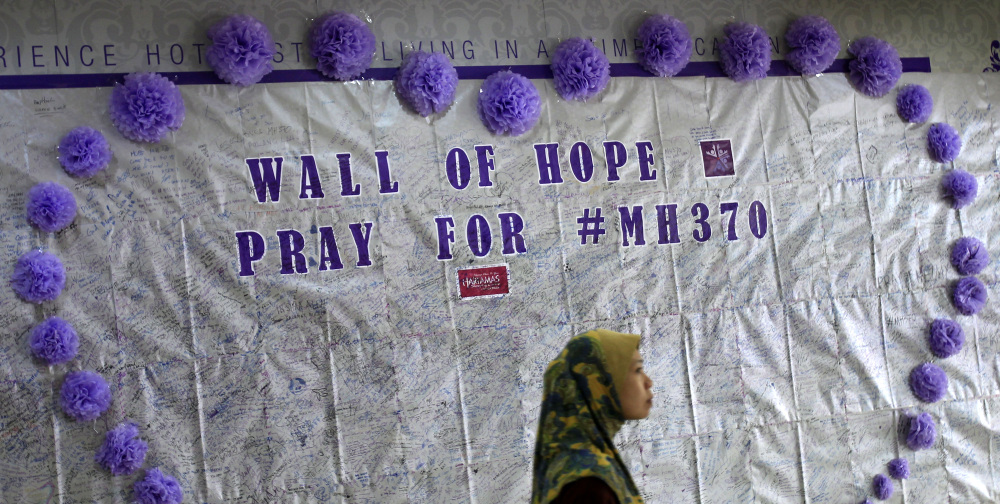 A woman walks past a message board for passengers aboard a missing Malaysia Airlines plane, at a shopping mall in Kuala Lumpur, Malaysia, Sunday.