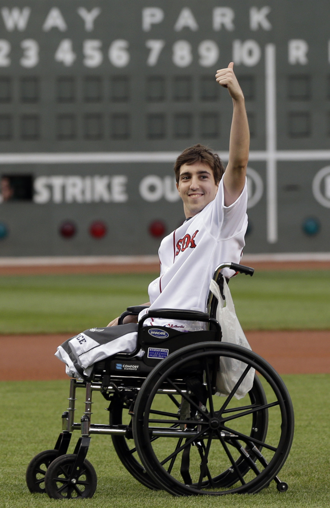 Boston Marathon bombing survivor Jeff Bauman acknowledges cheering fans before throwing out a ceremonial first pitch at Fenway Park on May 28, 2013, before the Red Sox played the Philadelphia Phillies.