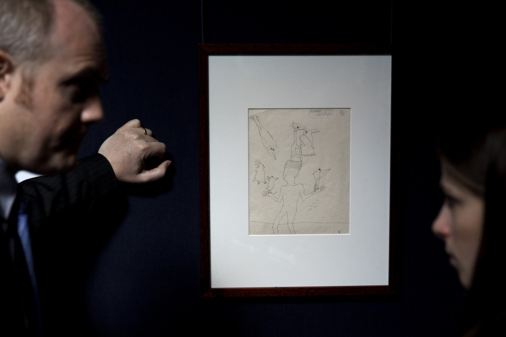 """A Sotheby's employee, left, speaks to a journalist beside an untitled illustration of a boy with six birds by the late Beatles members John Lennon at the auction house's premises in central London. The ink drawing in black with editorial notes is estimated to fetch between $19,795 to $24,744 in a June 4 New York sale of Lennon autograph drawings and manuscripts produced for his books """"In His Own Write"""" and """"A Spaniard in the Works""""."""