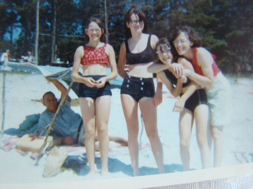 Eyeglass family: Amy Calder, second from right, with her mother, Frances Calder, hugging her. Her sister Jane is at far left, and sister Katherine in the middle. Amy's father, Edwin Calder, is under the umbrella. The photo was taken at Pemaquid Beach in the 1960s.