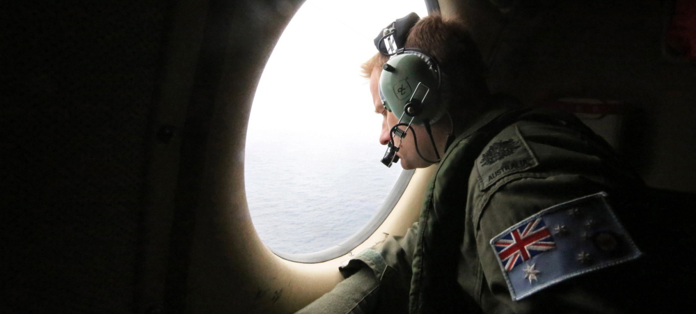 Royal Australian Air Force Warrant Officer Michal Mikeska looks for signs of a crashed airliner from a plane flying over the Indian Ocean.
