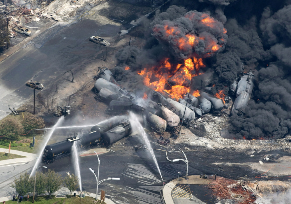 Photo from July 6, 2013 shows smoke rising from railway cars carrying crude oil that derailed in downtown Lac-Megantic, Quebec. A runaway train hurtled down an incline and slammed into downtown Lac-Megantic, where several railway cars exploded.