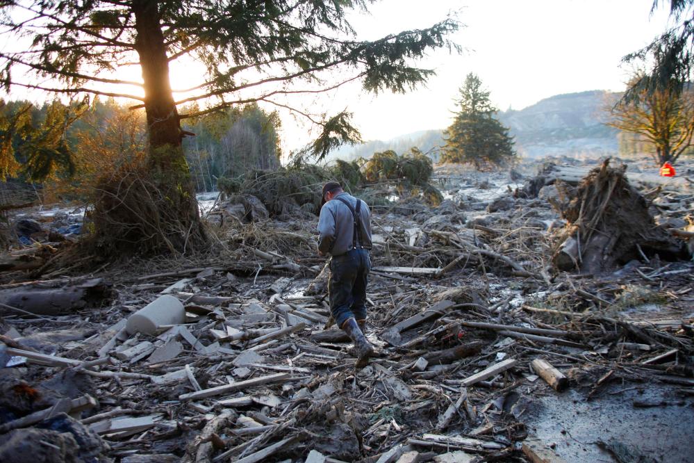 Steve Skaglund walks across the rubble on the east side of the fatal mudslide near Oso, Wash., on Sunday.