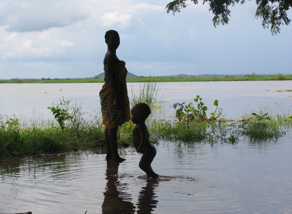 A woman and child wade in flood waters in Mutarara, Mozambique. Thousands of people who lost their homes in floods last year are at risk again as the rising Zambezi river waters threaten their resettlement camps.