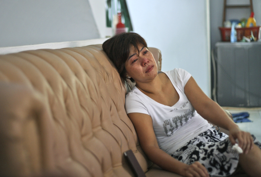 "Yenny, the sister of Sugianto Lo who was onboard the Malaysia Airlines plane MH370, weeps on the couch as she watches a news update on the search of the wreckage of the jetliner at their family residence in Medan, North Sumatra, Indonesia, Tuesday, March 25, 2014. After 17 days of desperation and doubt over the missing Malaysia Airlines jet, the country's officials said an analysis of satellite data points to a ""heartbreaking"" conclusion: Flight 370 met its end in the southern reaches of the Indian Ocean, and none of those aboard survived."