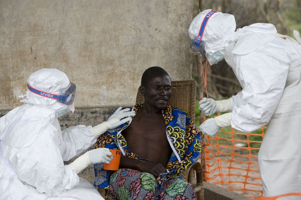 A Congolese patient, center, who was confirmed to have Ebola hemorrhagic fever is comforted by Doctors without Borders personnel in Kampungu, Kasai Occidental province, Congo, in September 2013. An outbreak of the deadly Ebola virus is believed to have killed at least 59 people in Guinea and may already have spread to neighboring Liberia, health officials said Monday.