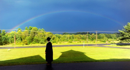 CHARTER SCHOOL: Cody Buzzell, 17, stands in the shadow of Moody Chapel as a rainbow shines over Hinkley before the Maine Academy of Natural Sciences at Good Will-Hinkley inaugural commencement last August.