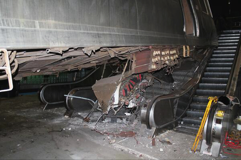 """This photo released Tuesday, March 25, 2014, by the National Transportation Safety Board shows the aftermath of a Chicago commuter train that crashed Monday at O'Hare International Airport when the train jumped off the tracks and climbed an escalator. An NTSB official said Wednesday that the operator of the train admitted she """"dozed off"""" before the accident."""