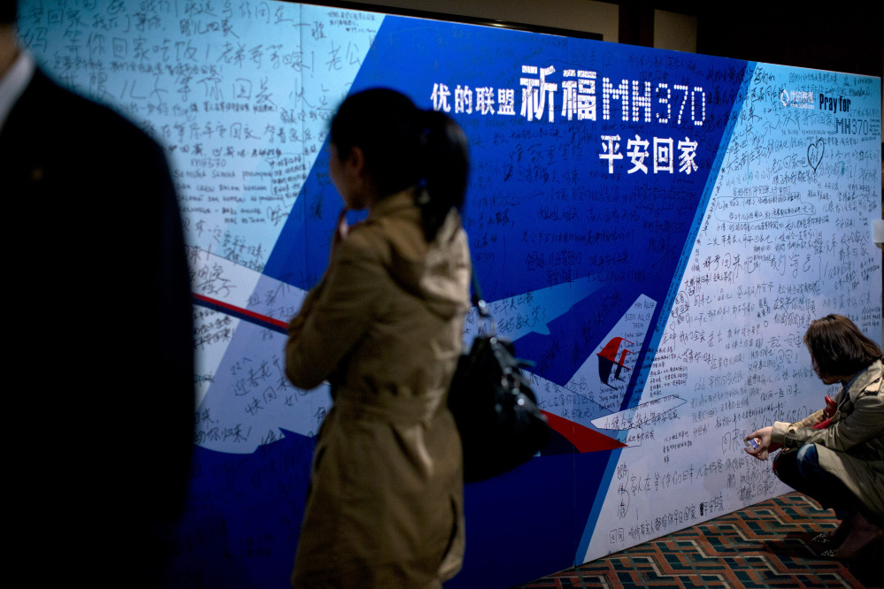 "Journalists read words from board covered by written wishes from relatives during a briefing meeting given by Malaysian officials at a hotel in Beijing, China, Wednesday, March 26, 2014. Some of the wishes read, ""Dear husband, you must stay strong, I am waiting for you. My dear, please be back soon."" The search of the missing plan resumed Wednesday after fierce winds and high waves forced crews to take a break Tuesday. A total of 12 planes and five ships from the United States, China, Japan, South Korea, Australia and New Zealand were participating in the search, hoping to find even a single piece of the jet that could offer tangible evidence of a crash and provide clues to find the rest of the wreckage."