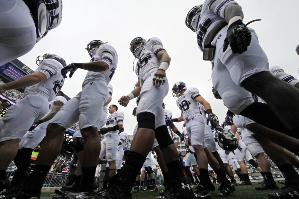 The Northwestern football team heads to the locker room after warming up before an NCAA game against Penn State in State College, Pa., in this Oct. 6, 2012, photo. A federal agency ruled Wednesday that the Northwestern football team can bargain with the school as employees represented by a union.