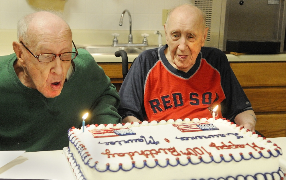 TWIN CENTENARIANS: Lawrence Binette, left, blows out his candle with his twin brother, Maurice Binette, on Thursday at an early 100th birthday party at the Maine Veterans' Home in Augusta.