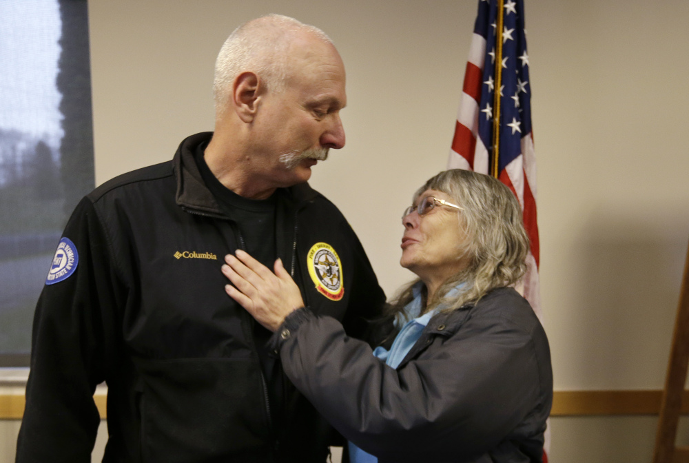 Robin Youngblood embraces Snohomish County helicopter crew chief Randy Fay, who helped rescue her from the deadly mudslide that moved her house a quarter-mile.
