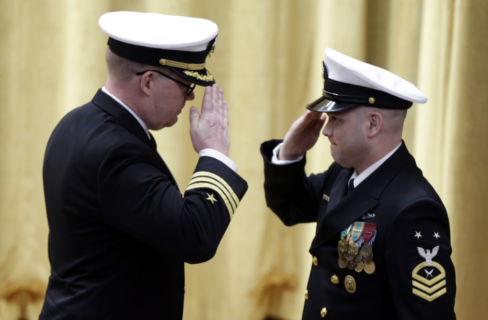 Cmdr. Rolf Spelker, left, salutes a sailor at the decommissioning ceremony for the fire-damaged USS Miami nuclear submarine at the Portsmouth Naval Shipyard on Friday in Kittery.