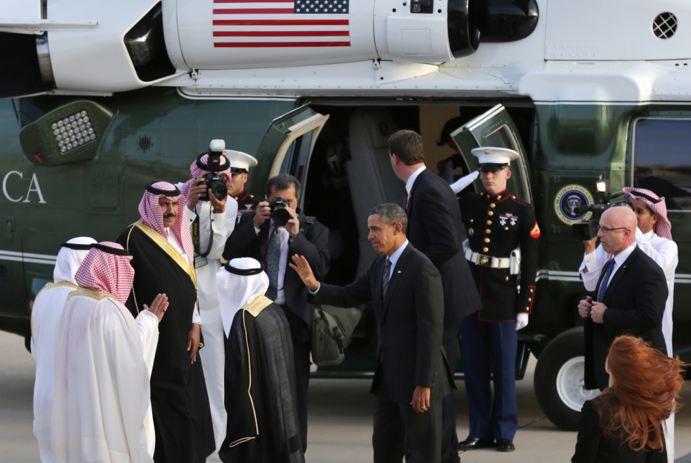 President Barack Obama waves to Governor of Riyadh Prince Khalid Bandar bin Abdul-Aziz Al-Saud and other Saudi officials next to his helicopter in Riyadh, Saudi Arabia, as the president prepares to travel to the Saudi king's desert compound Friday.