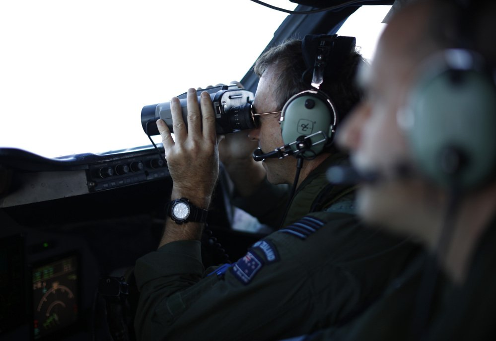 Wing Commander Rob Shearer looks through binoculars on the flight deck of a Royal New Zealand Air Force P-3K2 Orion aircraft searching for missing Malaysian Airlines flight 370 over the southern Indian Ocean, March 29, 2014.