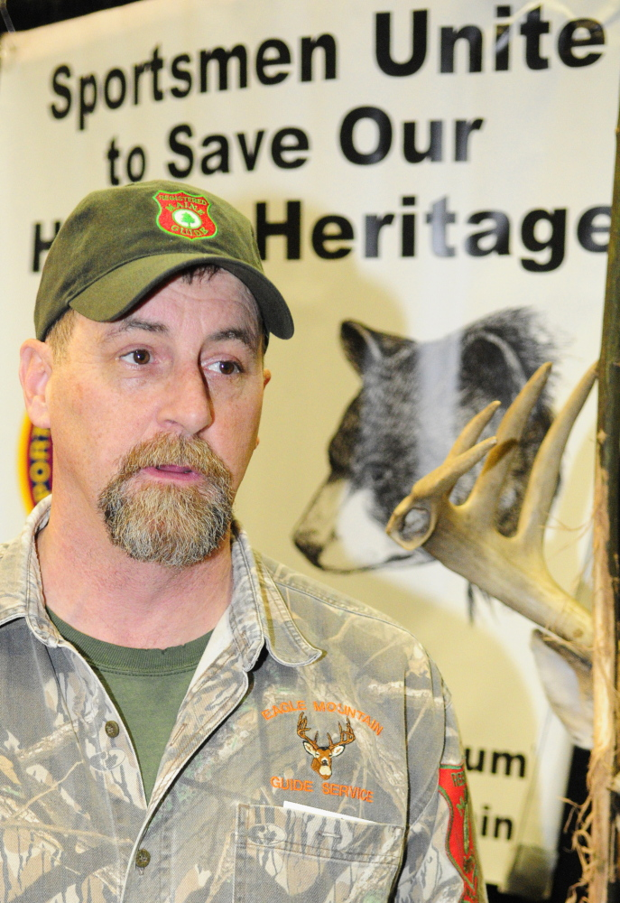 Jobs issue: Bear hunting guide Matt Whitegiver answers a question about the pending bear hunt referendum during an interview Saturday at the Maine Sportsman's Show in the Augusta Civic Center.