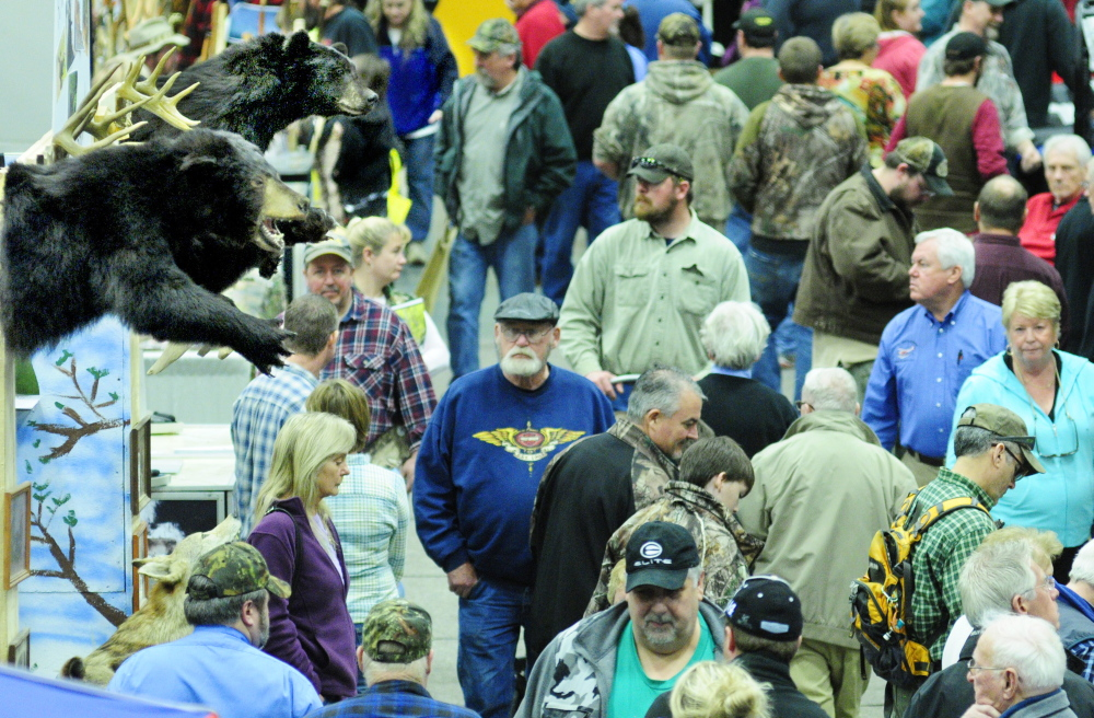 A symbolic presence: Showgoers walk past a booth with stuffed bears on display Saturday during the Maine Sportsman's Show in the Augusta Civic Center.