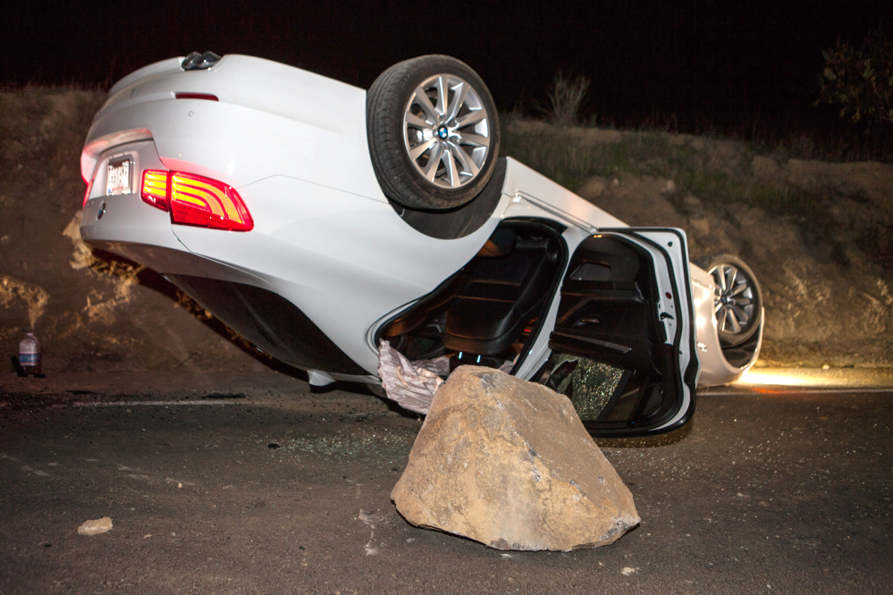A car overturned on a highway in the Carbon Canyon area of Brea, Calif., Friday night after hitting a rock slide caused by an earthquake. The people inside the car sustained minor injuries.