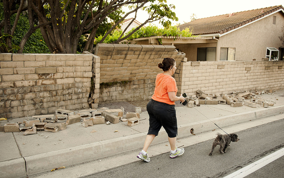A woman walks her dog past a broken block wall in Fullerton, Calif., on Saturday.