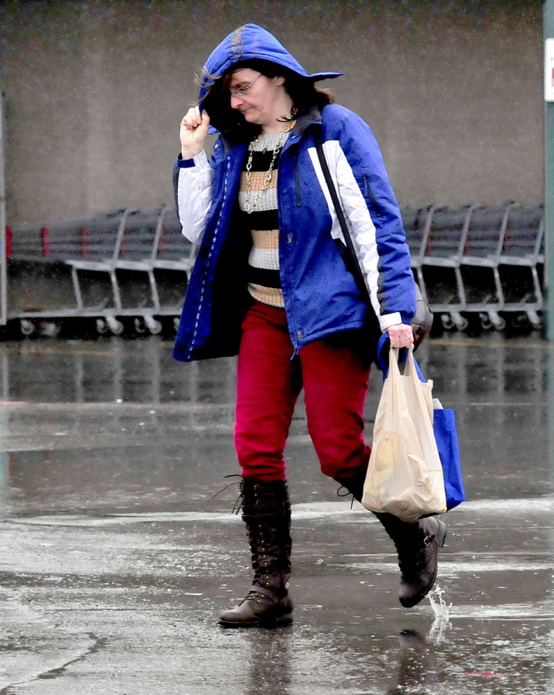 Staff photo by David Leaming LIQUID SNOW: Sarah Wright leans into the blowing rain and shields her face with a hood at Elm Plaza inWaterville on a wet Sunday, March 30, 2014.