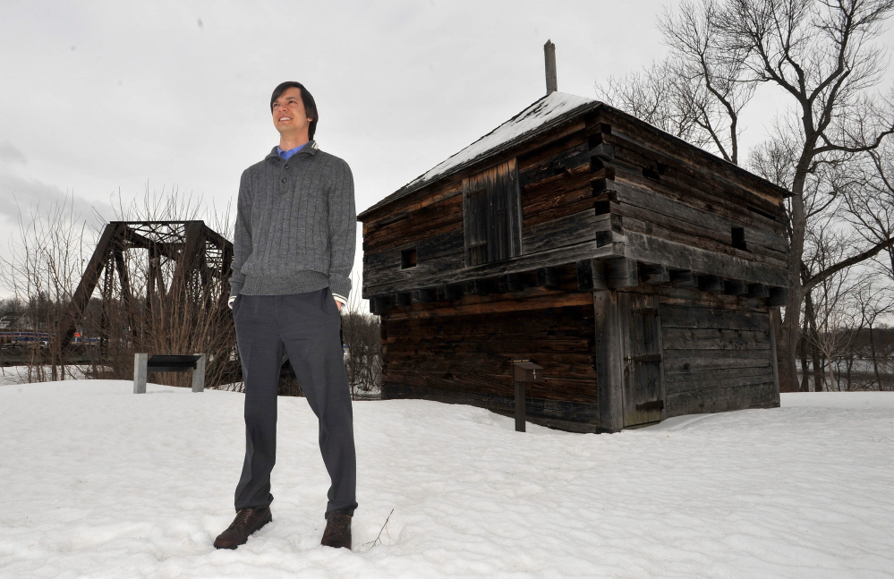 BIT OF HISTORY: Colby College history professor Daniel Tortora, 32, stands at Fort Halifax Park on Friday afternoon with the reconstructed blockhouse behind him. Tortora recently completed a book detailing the history of Fort Halifax. The book is scheduled to be released Tuesday.