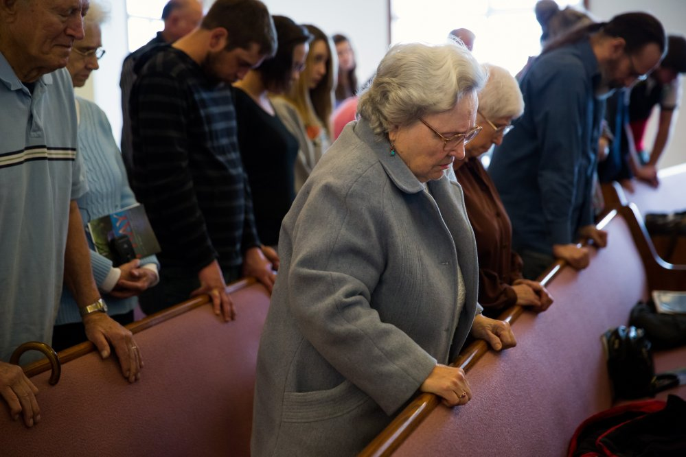 Rose Fagerberg, center, bows her head in prayer during Sunday church service at the Glad Tidings Assembly of God, in Darrington, Wash.