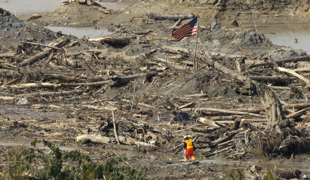 A searcher walks through a channel of water as a flag flies in the debris field Monday near Darrington, Wash., at the site of the massive mudslide that hit the nearby community of Oso,Wash., on March 22.