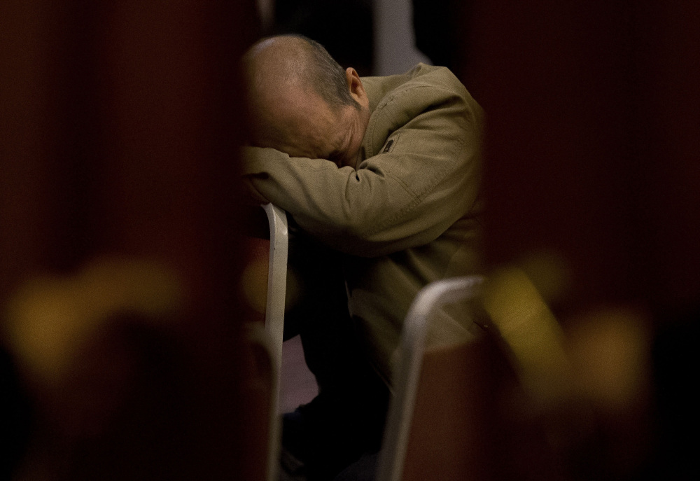 In this March 18, 2014 file photo, a relative of Chinese passengers aboard the missing Malaysia Airlines Flight MH370 rests on a chair as he waits for a news briefing by the Airlines' officials at a hotel ballroom in Beijing, China. Malaysia's credibility in the hunt for FLight 370 is being challenged again, especially by relatives of Chinese passengers.