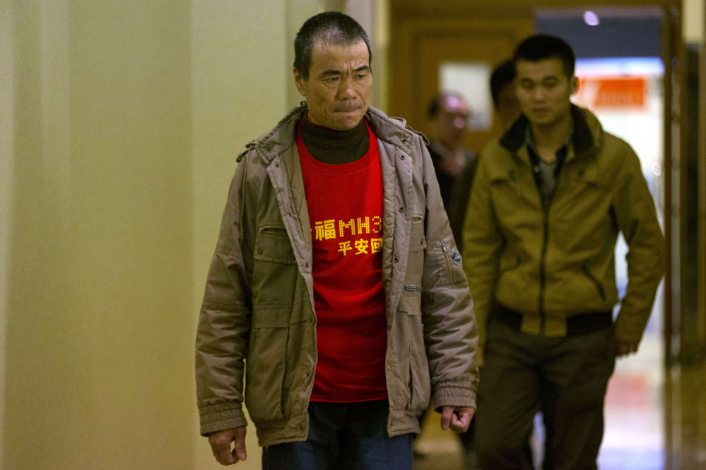"""A relative of Chinese passengers onboard Malaysia Airlines Flight 370 wears a t-shirt which reads """"Pray for MH370 safe return"""" as he arrives to attend a closed door meeting with Malaysian officials via teleconference at a hotel in Beijing, China, Wednesday, April 2, 2014. A Malaysian police investigation into the pilots of the missing Malaysian jet might turn up nothing, the force's chief said Wednesday, while the head of the international search effort also acknowledged that an air hunt to spot wreckage on the surface of the southern Indian Ocean was not certain of success."""
