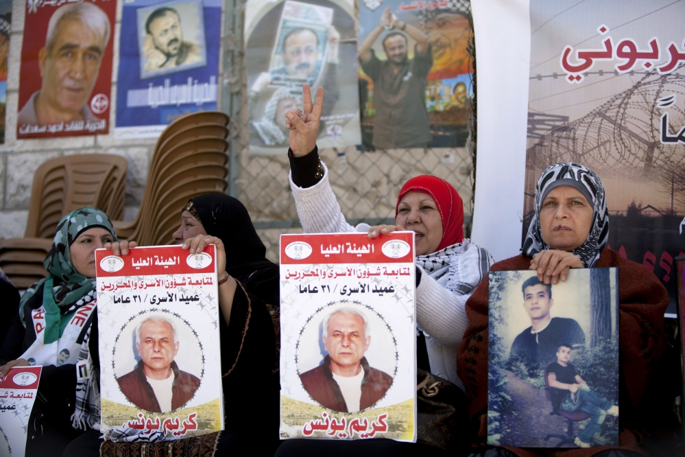 "Women hold portraits of Palestinian prisoners held in Israeli jails during a rally calling for their release in the West Bank city of Ramallah on Tuesday. Arabic on the posters reads, ""Dean of prisoners, Karim Younis, 21 years in prison."""