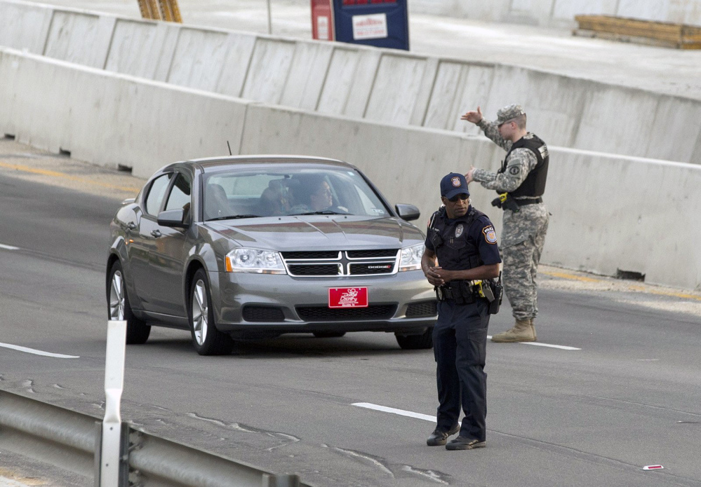 Vehicles are checked outside of the Bernie Beck Gate, Wednesday, April 2, 2014, in Fort Hood, Texas. One person was killed and 14 injured in a shooting at Fort Hood, and officials at the base said the shooter is believed to be dead.