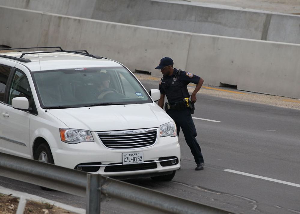 A police officer checks drivers' IDs outside the main gate at Fort Hood, Texas, after a shooting at the Army base Wednesday, April 2, 2014. At least one person was killed and at least 14 injured in a shooting Wednesday at Fort Hood.