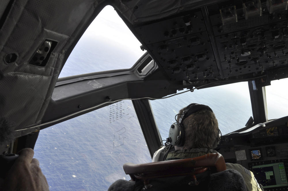 In this photo made available Thursday, April 3, 2014, a crewman on a Royal New Zealand Air Force P-3 Orion Rescue Flight 795 searches for debris from the missing Malaysia Airlines Flight MH370, in southern Indian Ocean, 1,500 kilometers northwest of Perth, Australia.